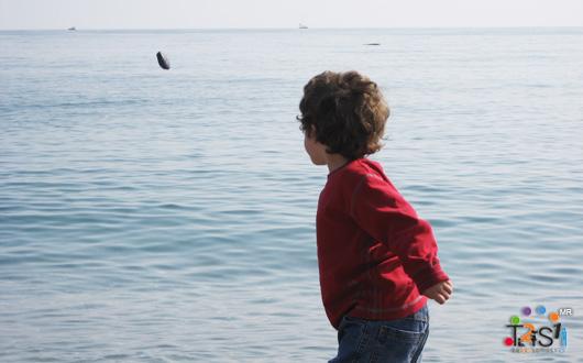Niño lanzando piedras en el agua