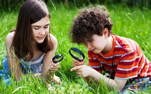 Niños observando el jardín con una lupa