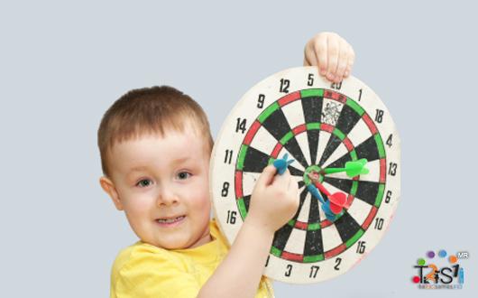 Niño jugando dardos