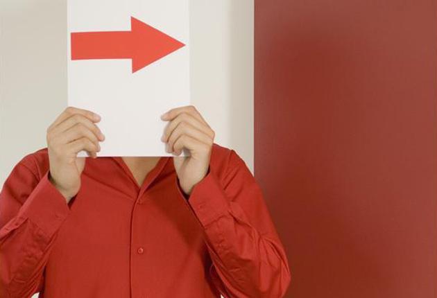 Hombre cubriéndose la cara con una hoja de papel