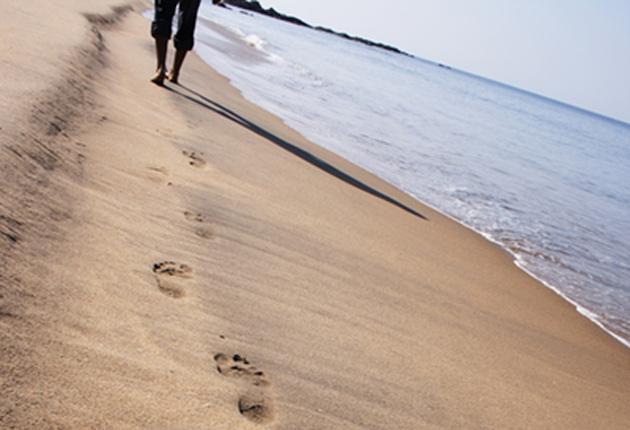 Huellas de un hombre sobre la arena del mar