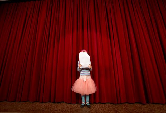 Niña en un escenario de teatro cubriéndose el rostro