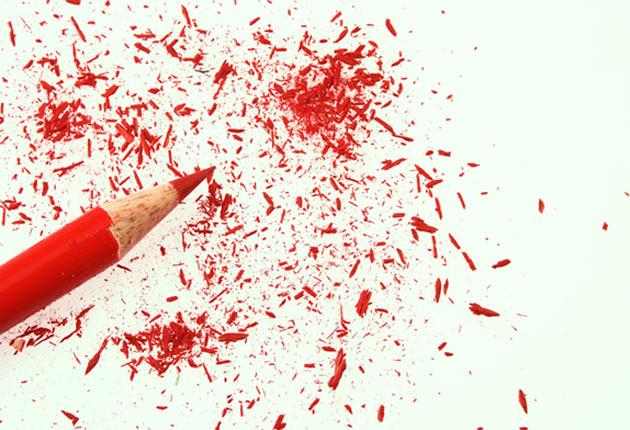 Lápiz rojo despuntado sobre hoja de papel blanca