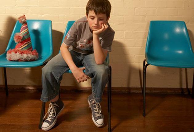 Niño sentado solo en una fiesta de cumpleaños