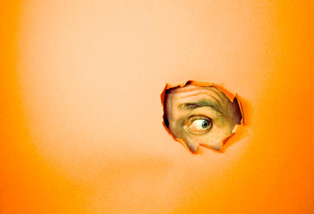 Hombre mirando a través de un hoyo en una hoja de papel