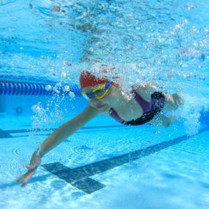 Niña nadando en una alberca olímpica