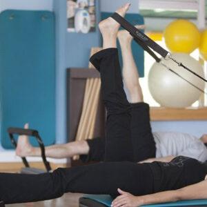 Personas haciendo ejercicio en cama de pilates.