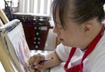 Chica con síndrome de Down dibujando