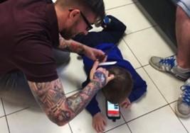 Peluquero se tira al suelo para que niño con autismo se sienta cómodo durante su corte de cabello